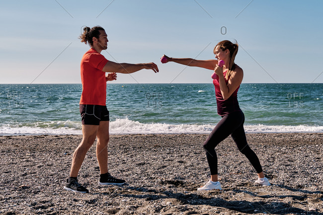 Side view of fit female athlete doing exercises with dumbbells and practicing punches under supervision of professional personal male trainer while standing on seashore