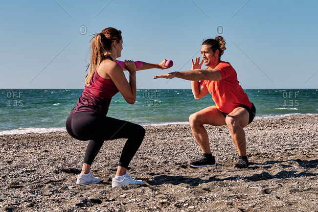 Side view of fit female athlete doing exercises with dumbbells and practicing punches under supervision of professional personal male trainer on seashore