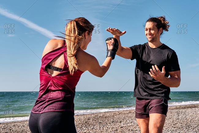 Strong man and woman punching each other while standing on beach during kickboxing workout near sea