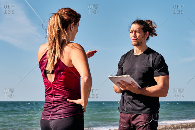 Fit female athlete in sportswear standing at seaside during workout and having conversation with personal instructor taking notes in notebook