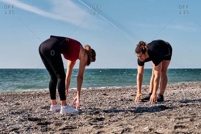 Side view of flexible female athlete doing forward bends while standing on beach near sea with personal instructor and warming up muscles before active workout