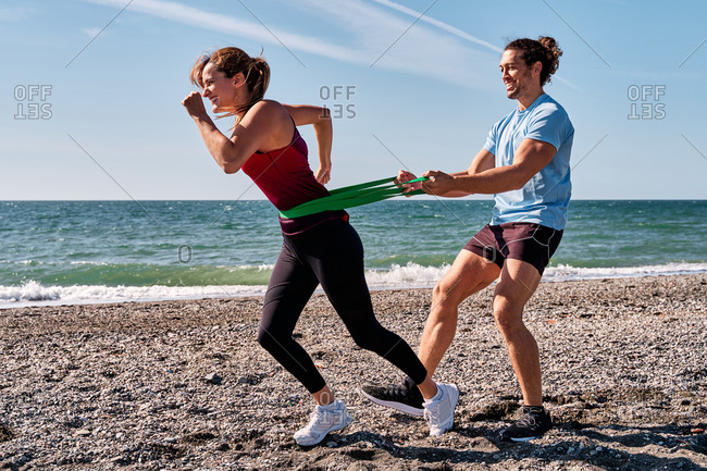 Side view of strong cheerful woman running with resistance band and help of male personal trainer on seashore on sunny day during active workout