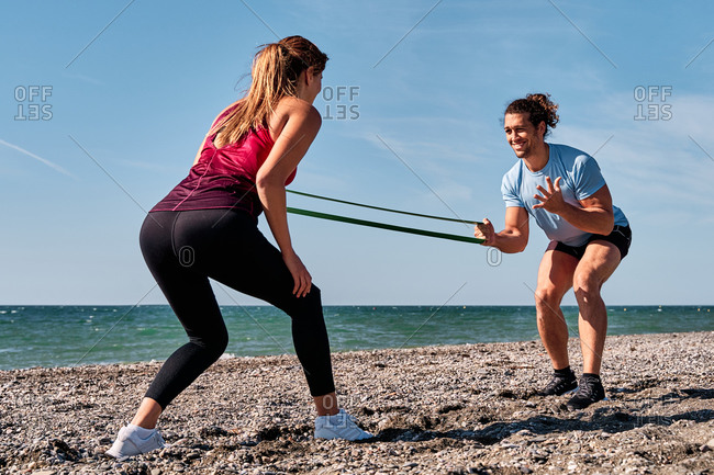 Unrecognizable female athlete doing squats with elastic band and help of personal instructor during workout at seaside in summer