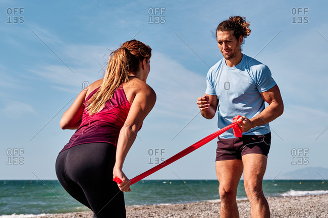 Unrecognizable crop female athlete doing squats with elastic band and help of personal instructor during workout at seaside in summer