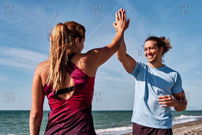 Friendly sportsman and sportswoman giving high five after workout while standing on seashore and looking at each other