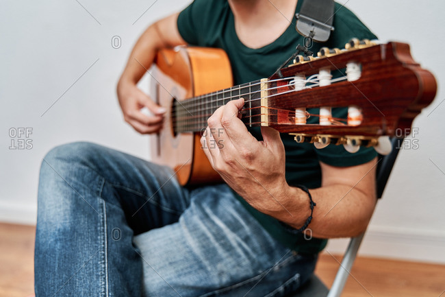 Cropped unrecognizable focused male guitarist in jeans playing acoustic guitar while sitting on chair at home