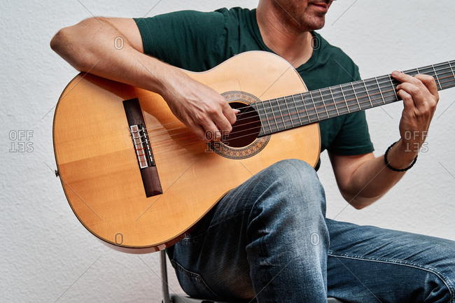 Cropped unrecognizable focused male guitarist in jeans playing acoustic guitar while sitting on chair at home on white background