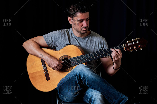 Focused male guitarist in jeans playing acoustic guitar while sitting on chair at home