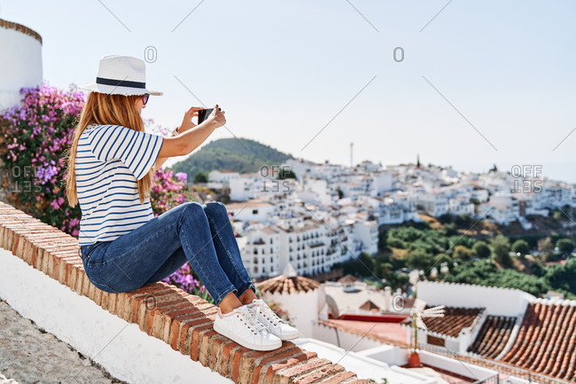 Side view of female traveler sitting on stone fence on hill and taking picture on smartphone of city of Frigiliana during summer vacation