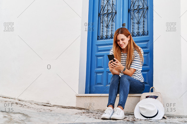 Low angle of positive female traveler sitting on steps near door on old street and browsing smartphone during summer holiday in Frigiliana