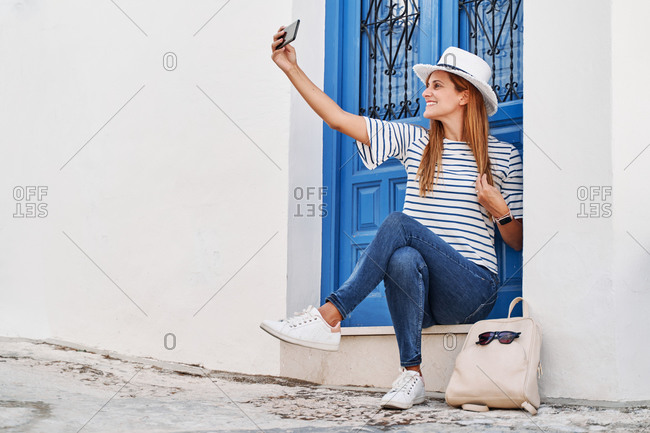 Low angle of positive female traveler sitting on steps near door on old street and taking photo during summer holiday in Frigiliana