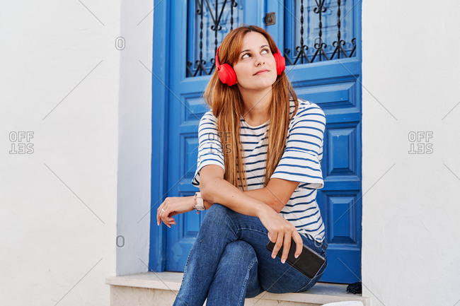 Carefree female listening to calm music in headphones while sitting with smartphone on doorstep on street and dreamily looking up