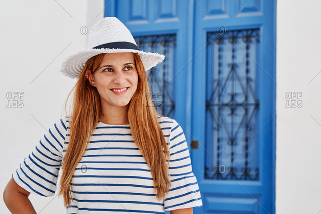 Charming female tourist in stylish sunhat and striped t shirt standing on street in Frigiliana and looking away while enjoying summer holiday