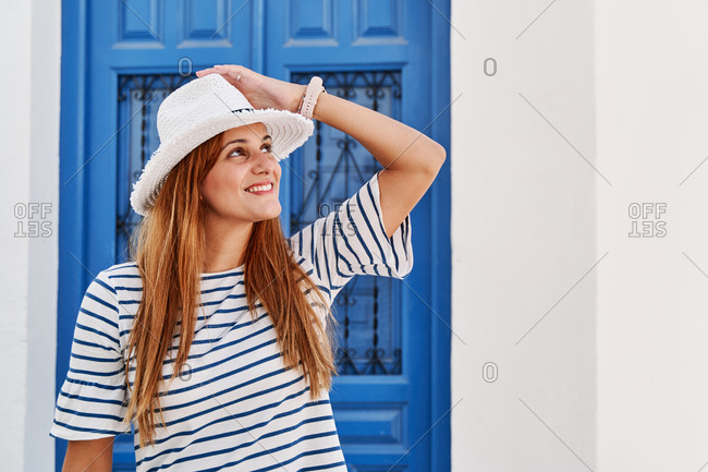 Charming female tourist in stylish sunhat and striped t shirt standing on street in Frigiliana and looking up while enjoying summer holiday