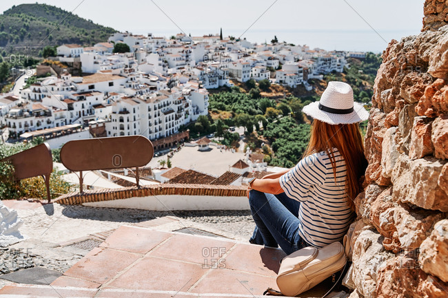 Back view of delighted female tourist sitting on stone border enjoying freedom on background of cityscape of Frigiliana during vacation in summer