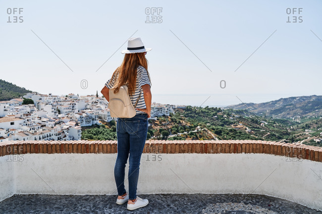 Back view of anonymous female traveler standing on terrace at viewpoint and admiring spectacular cityscape of Frigiliana on sunny day in summer