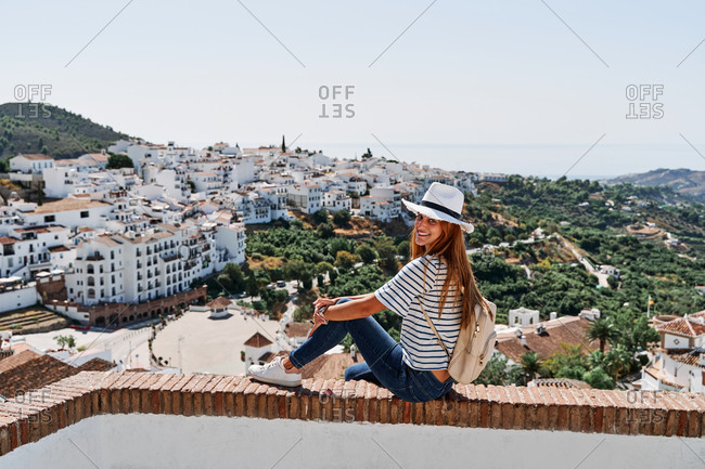 Delighted female tourist sitting on stone border enjoying freedom on background of cityscape of Frigiliana during vacation in summer