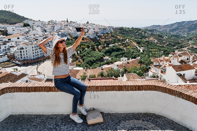 Side view of delighted female tourist in sunhat and sunglasses taking photo on selfie camera of smartphone on background of cityscape of Frigiliana during summer vacation