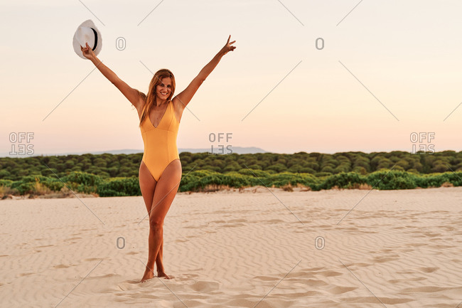 Full body of barefoot delighted female wearing swimwear raising arms up while enjoying freedom on sandy shore