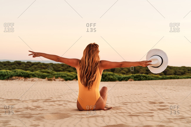 Back view of anonymous delighted female wearing swimwear sitting and raising arms up while enjoying freedom on sandy shore