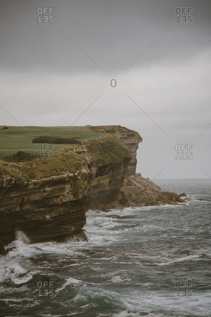 Scenic landscape of rocky cliff near stormy sea under gray sky in overcast weather
