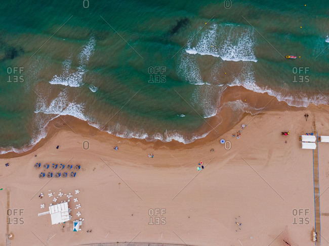 Magnificent aerial view of turquoise sea waving on sandy coastline with deckchairs and umbrellas in summer