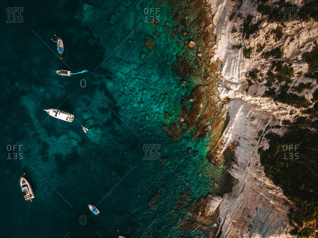 Breathtaking drone view of modern motor boats floating on calm surface of clean turquoise sea near rocky coastline