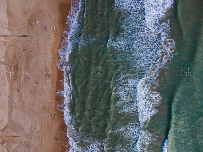 Magnificent aerial view of turquoise sea waving on sandy coastline in summer