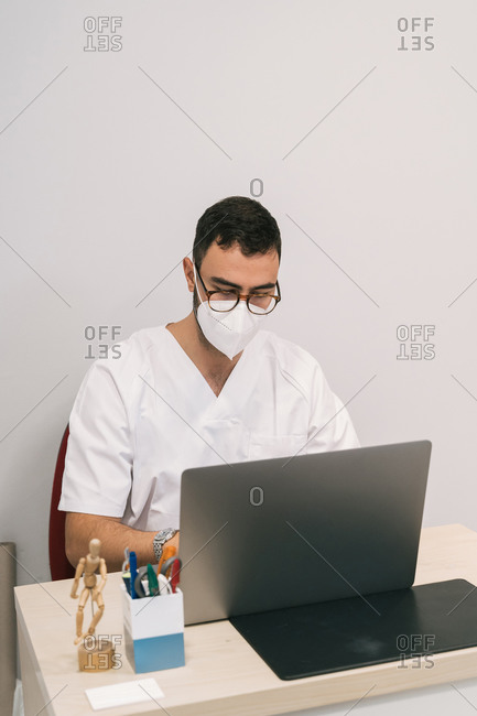 High angle of busy male physician in medical mask sitting at table and working on laptop in modern clinic