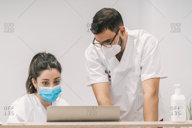 Concentrated practitioners in medical masks working together on laptop in bright modern clinic