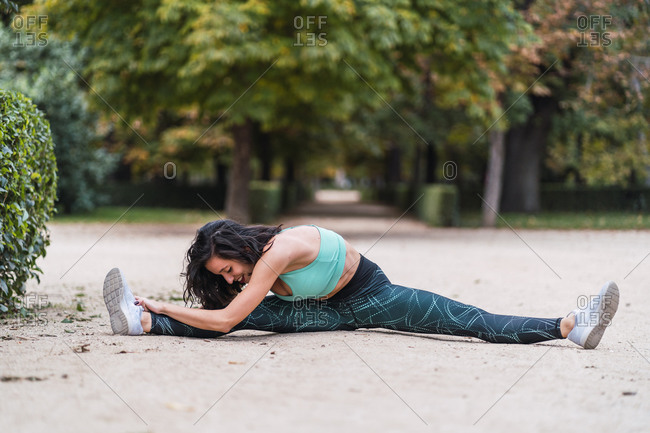 Smiling sportswoman sitting in park and stretching legs while doing splits and warming up during workout