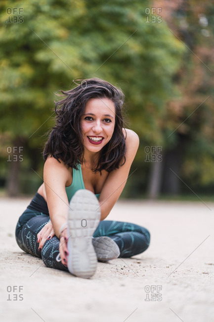 Slim female athlete in sportswear sitting on the ground in park while stretching body before training and looking at camera