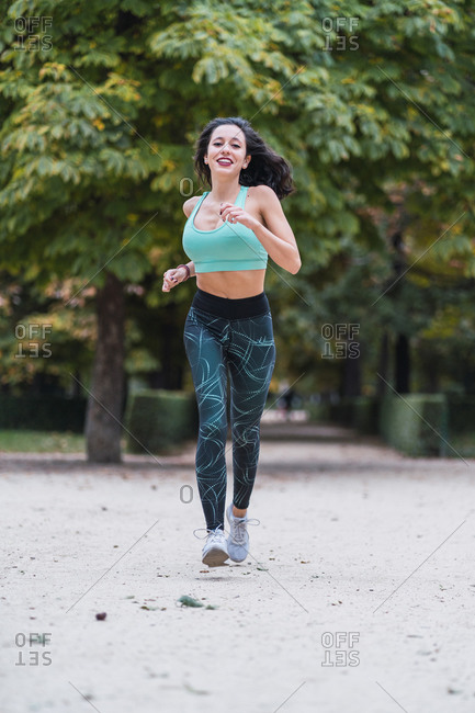 Full body of slim female running along path in park while doing cardio training and looking at camera