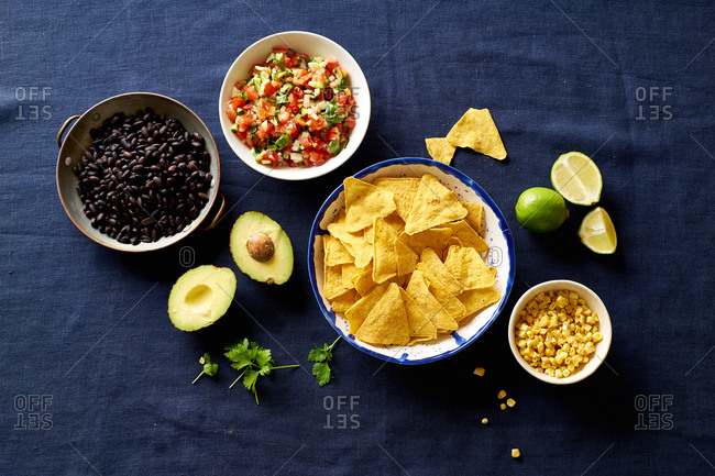 Ingredients for cooking chilaquiles - black beans, tortilla chips, corn and salsa