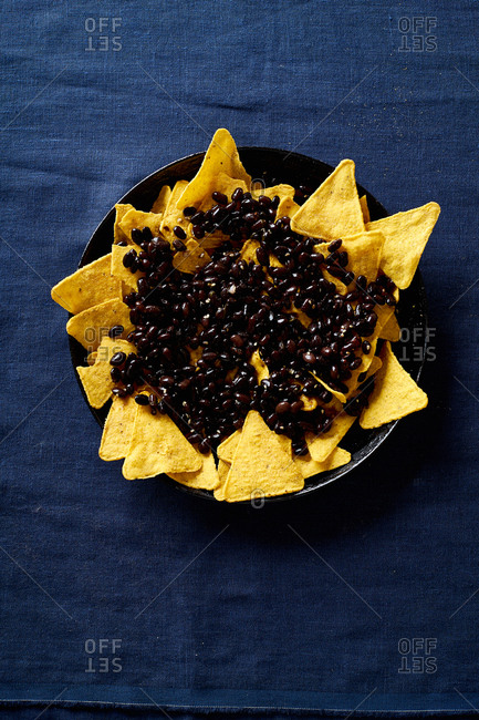 Cooking chilaquiles - Mexican breakfast made of black beans, corn, tortilla chips and fried eggs