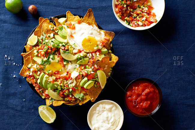 Chilaquiles Mexican breakfast made of black beans, corn, tortilla chips and fried eggs