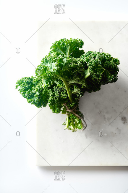A bunch of green curvy kale tied with twine on white background