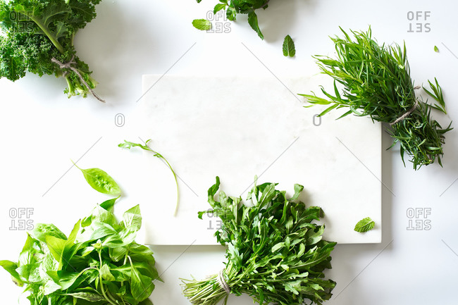 Flat lay with various herbs and lettuce and marble cutting board on white background