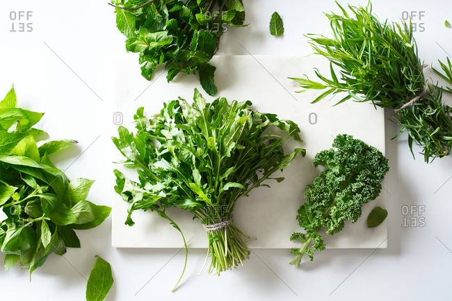 Flat lay with various herbs and lettuce and marble cutting board