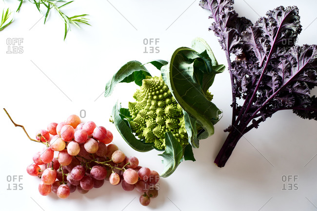 Flatlay with purple kale, pink grapes and romanesco cabbage