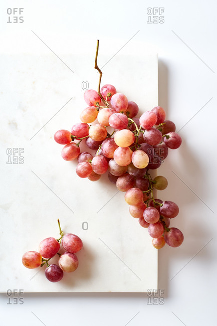 A cluster of pink muscatel grapes on white background