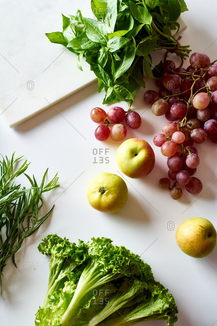 Flatlay with various vegetarian cooking ingredients: grapes, lettuce, apples and herbs