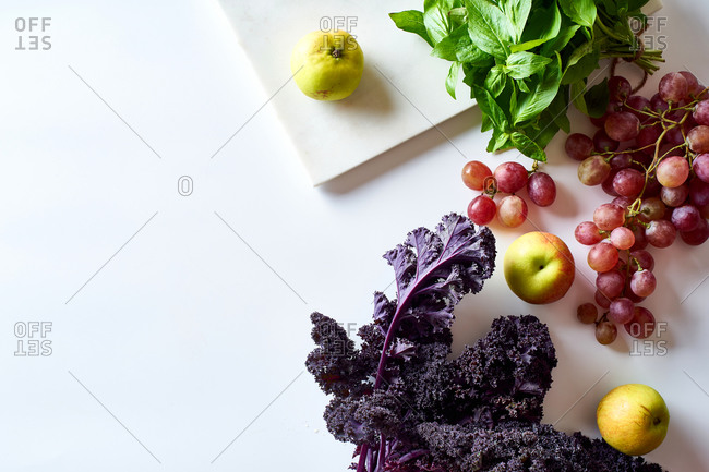 Flatlay with various vegetarian cooking ingredients: grapes, lettuce, kale and herbs