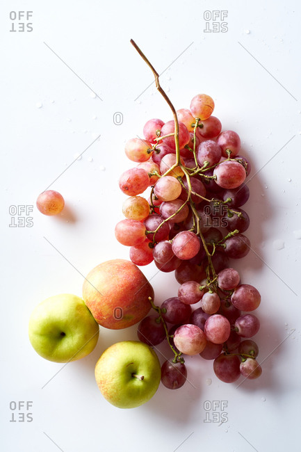 Pink muscatel grapes and apples on white background