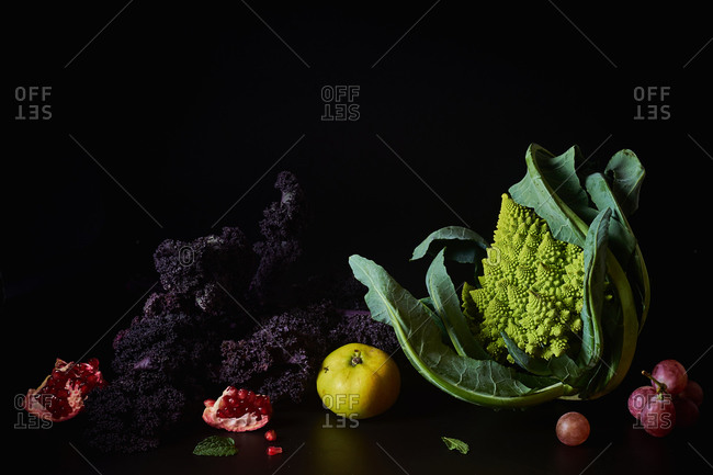 Still life with various vegetarian meal ingredients on dark background