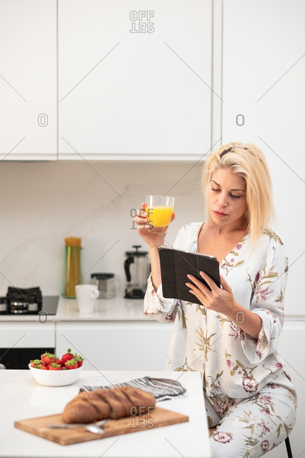 Tranquil female in silk pajama sitting at table in kitchen and browsing tablet while having breakfast in morning