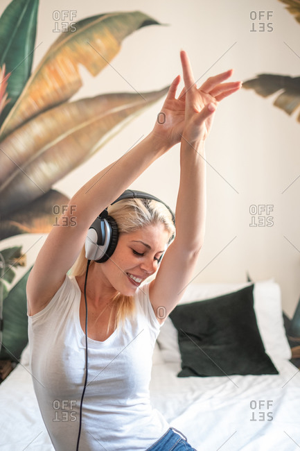 Dreamy female in headphones sitting on bed and enjoying songs with closed eyes and raised arms while entertaining at weekend