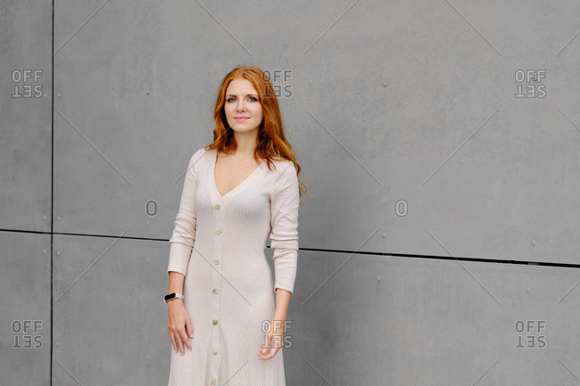 Positive young female with long red hair wearing casual dress and smart bracelet looking at camera while standing against concrete wall