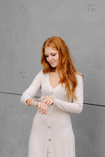 Red haired female in casual outfit standing on street and checking information on smart bracelet