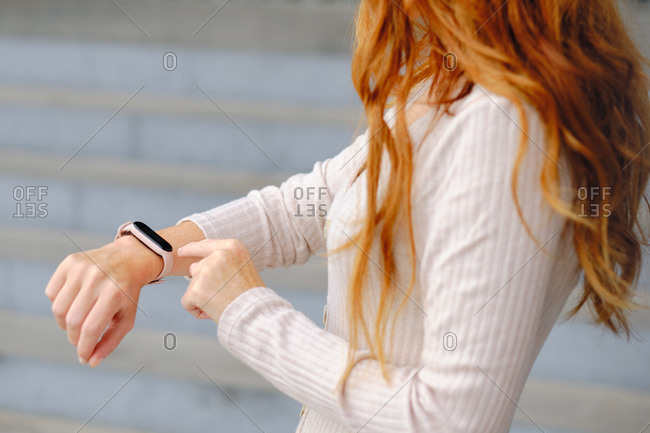 Side view of crop red haired unrecognizable female in casual outfit standing on street and checking information on smart bracelet